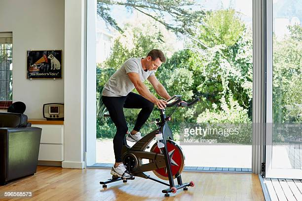 man working out on exercise bike at home - peloton stock pictures, royalty-free photos & images