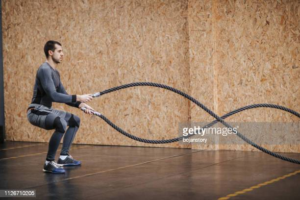man working out with battle ropes at a gym - battle stock pictures, royalty-free photos & images
