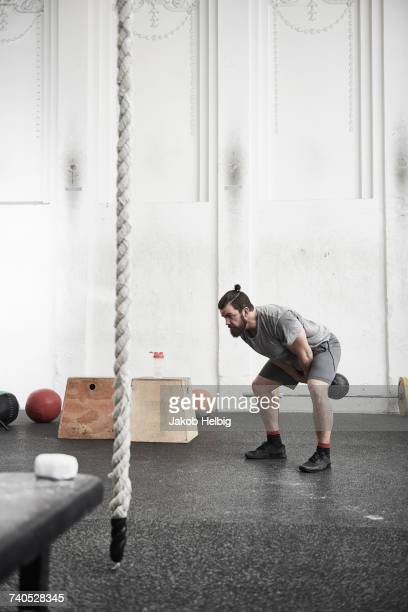 Man working out with kettlebell in cross training gym