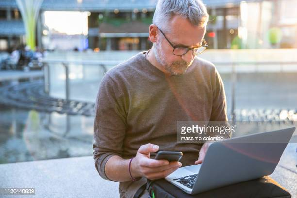 man working outdoor with laptop and smart phone - candid forum stock pictures, royalty-free photos & images