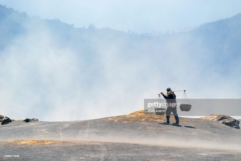 Man working over volcano's smoke at Bromo Tengger Semeru National Park, Indonesia : Stock Photo