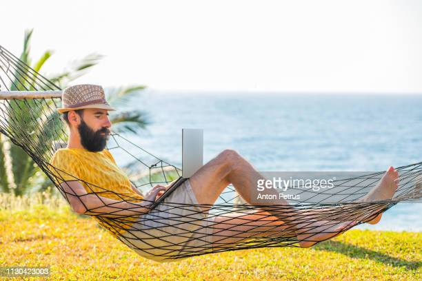 Man working with a laptop, on a hammock near the beach.