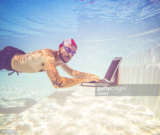 Man working with a laptop underwater