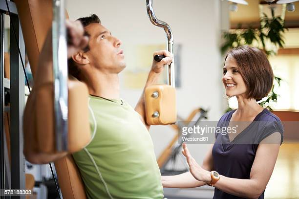 Man working with coach in fitness studio