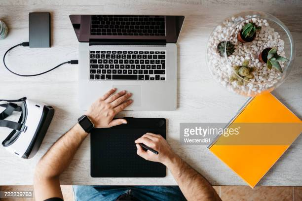 Man working with graphics tablet and laptop at home office, top view