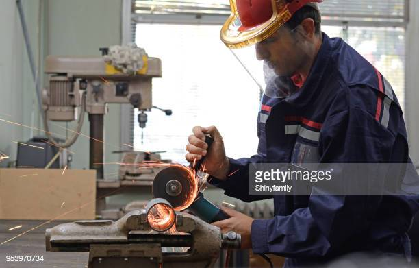 man working with grinder in workshop - helmet visor stock pictures, royalty-free photos & images