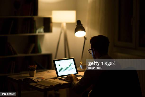 Man working with laptop late at night at home