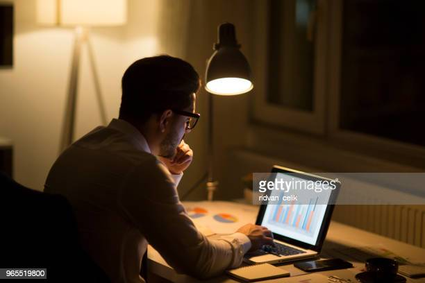 man working with laptop late at night at home - working overtime stock pictures, royalty-free photos & images