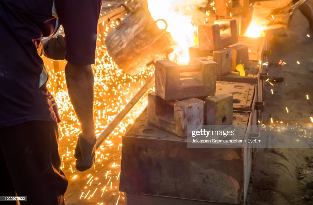 Man Working With Liquid Metal At Night : Stock Photo