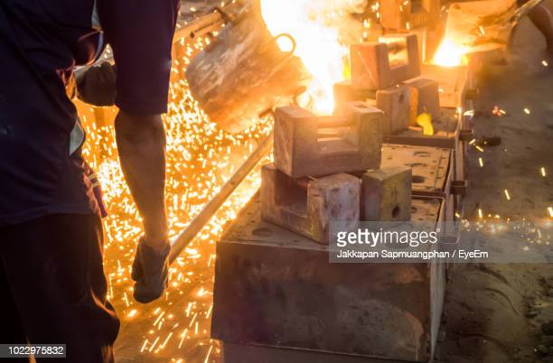 man working with liquid metal at night - steelmaking stock photos and pictures