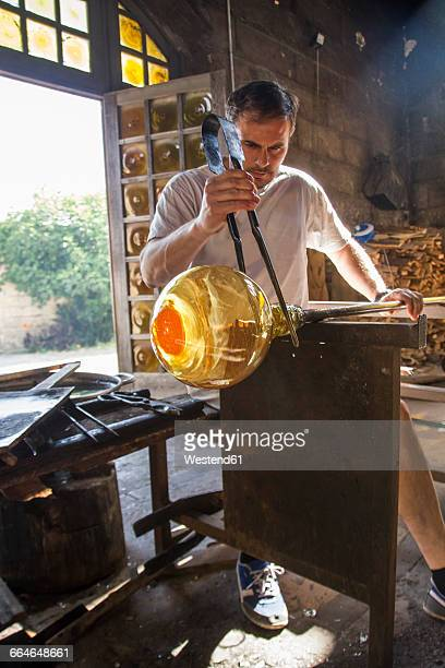 Man working with molten glass using a tweezers in a glass factory