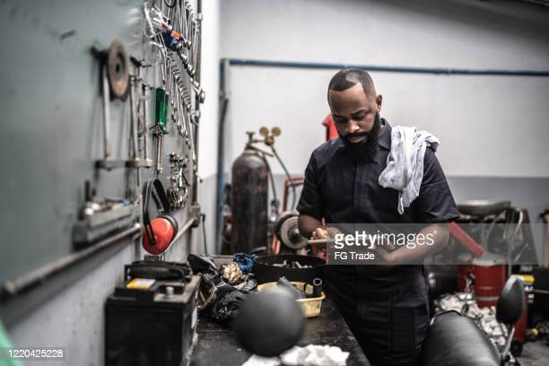 man working with tablet in auto repair - mechanic stock pictures, royalty-free photos & images