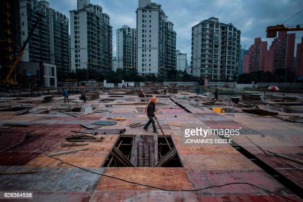 TOPSHOT A man works at a construction site of a residential skyscraper in Shanghai on November 29 2016 Chinese household debt has risen at an...