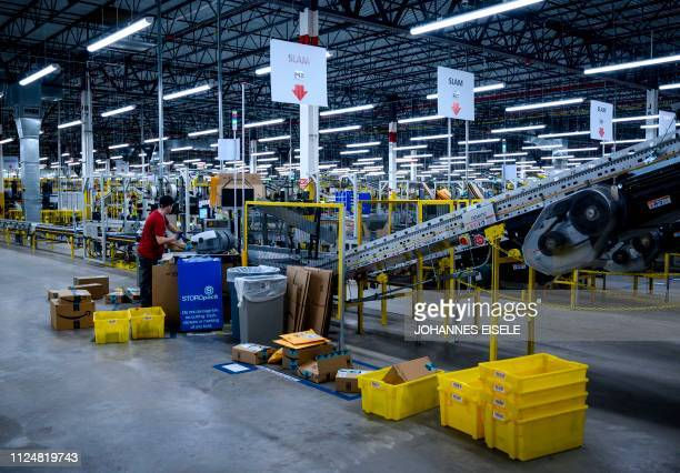 A man works at a conveyor belt at the 855000squarefoot Amazon fulfillment center in Staten Island one of the five boroughs of New York City on...