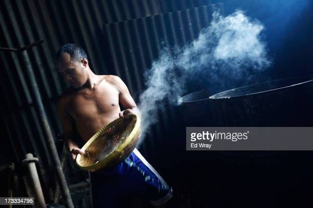 A man works at a small tempeh factory on July 12 2013 in Jakarta Indonesia Tempeh is an Indonesian staple made from fermented soy beans The...