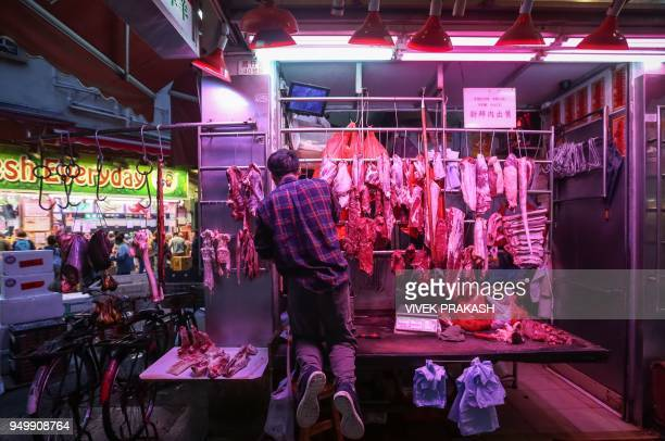 A man works at a stall selling meat at a street market in Hong Kong on April 22 2018