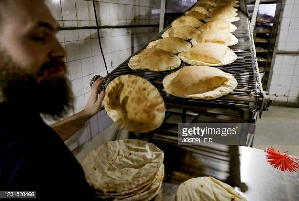 Man works at bakery that makes traditional flatbread in the Lebanese capital Beirut, on February 26, 2021. - Lebanon is locked in its worst economic...