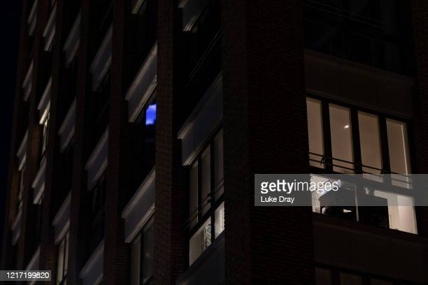 A man works at his computer inside a residential tower block on April 03 2020 in London England People have been forced to stay at home due to social...