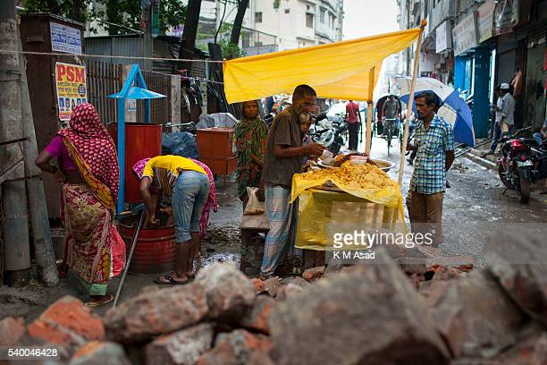 OLD DHAKA DHAKA BANGLADESH A man works at his temporary food stall in the street during a rainy day the first day of Ramadan in old Dhaka Bangladesh...