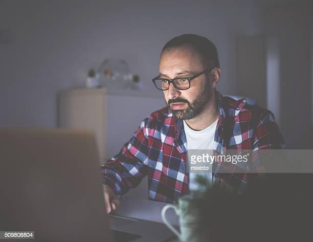 Man works at night on lap top