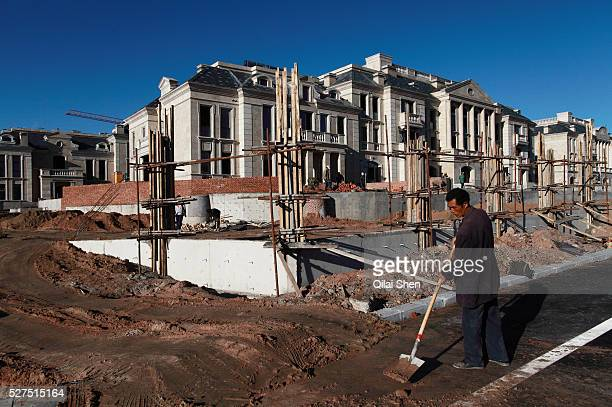 A man works at the site of a new luxury housing development being built in the middle of the dessert near the Kangbashi New District of Ordos City...