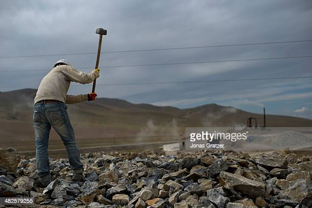 Man works hard at a mine to break rocks on the outskirts of the Sharyngol district in Mongolia where virtually everyone in the city works in the...