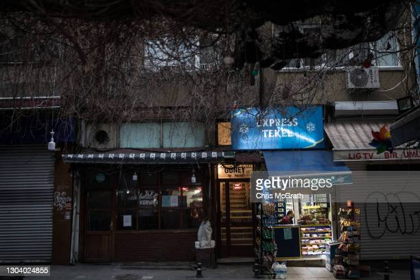 Man works in a shop selling alcohol next to a closed cafe in the Kadikoy district on February 24, 2021 in Istanbul, Turkey. Over the past few years,...