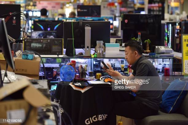 A man works in a store selling computer equipment in Beijing on May 8 2019 China's exports fell more than expected in April while imports rose...