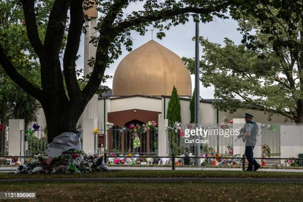 Man works inside Al Noor mosque as an armed police officer patrols the area outside where flowers and tributes have been paid, on March 22, 2019 in...