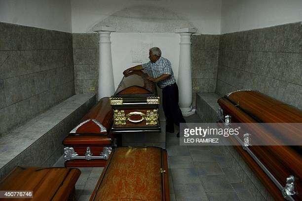 A man works on a coffin at a mortuary in Caracas on June 17 2014 AFP PHOTO/ LEO RAMIREZ