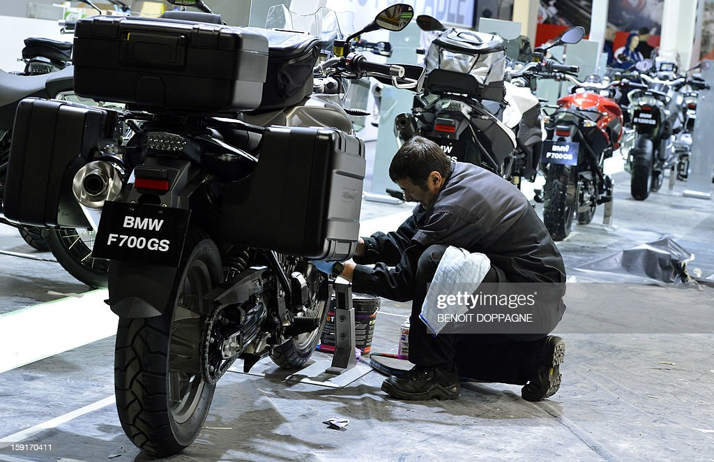 A man works on a motorcycle during preparations for the 91th edition of the European Motorshow Brussels, which will open to the press tomorrow and to the public from January 11 to 20, at the Brussels Expo center, on January 9, 2013.