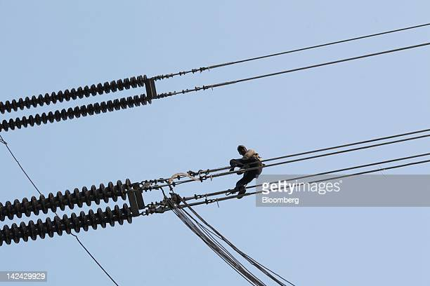 A man works on a power transmission cable in Tezpur India on Thursday March 29 2012 Prime Minister Manmohan Singh's government plans to attract $1...