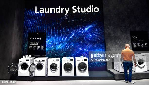 A man works on a set of washing and drying machines at the booth of Siemens at the consumer electronics fair IFA in Berlin on August 30 2017 The fair...