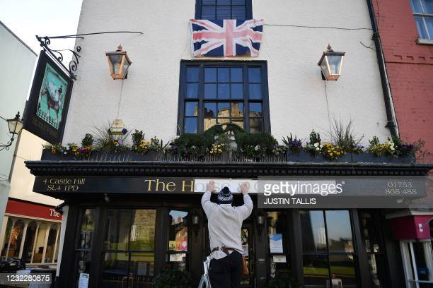Man works on a sign outside The Horse and Groom pub near Windsor Castle in Windsor, west of London, on April 13 following the April 9 death of...