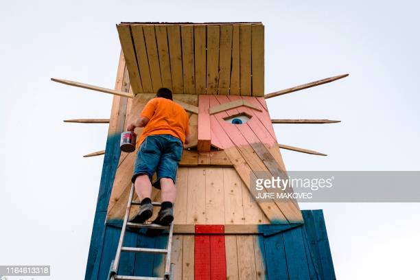Man works on a wooden statue made to resemble US President Donald Trump in the village of Sela pri Kamniku, about 20 miles northeast of Ljubljana in...