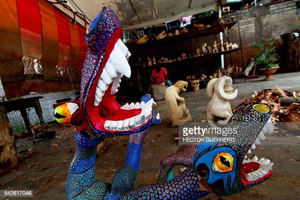 A man works on Alebrijes in a crafts workshop in San Antonio Arrazola Oaxaca State Mexico on 22 June 2016 Alebrijes are coloured Mexican folk art...