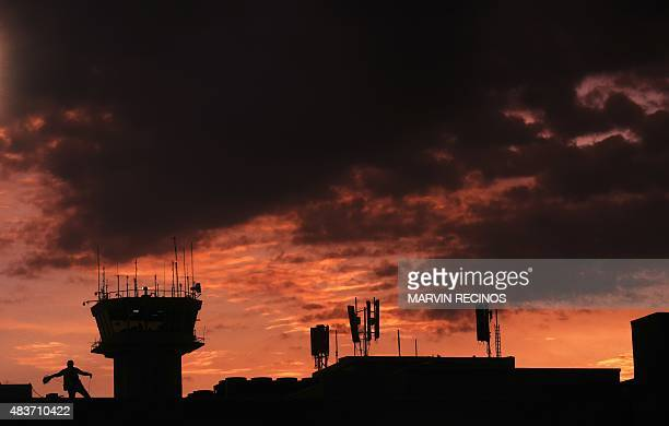 A man works on an tower at the Monsignor Oscar Romero international airport in San Luis Talpa 45 km south of San Salvador on August 11 2015 AFP PHOTO...