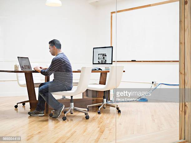Man works on laptop in conference room