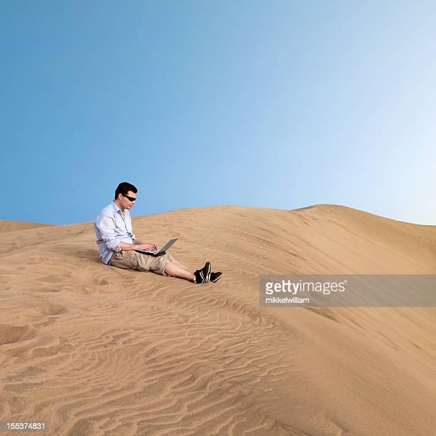 Man works on laptop in the desert