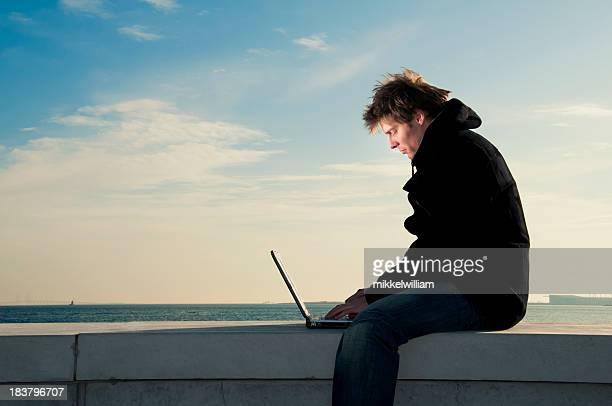 Man works on laptop near the sea