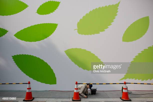 A man works on the pavement in front of the construction wall of the new Apple store at Omotesando on June 4 2014 in Tokyo Japan The new store will...