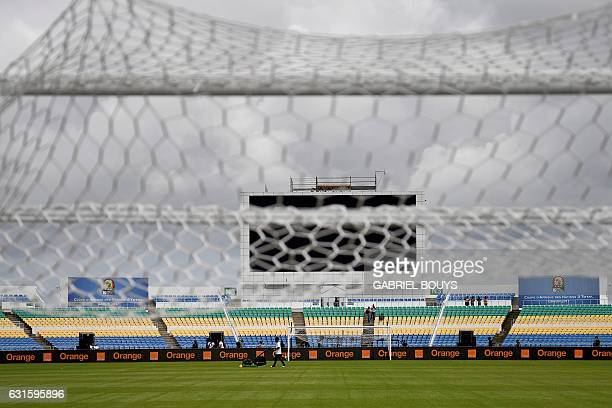 A man works on the pitch of the Stade de lAmitié Sinogabonaise Stadium in Libreville on January 13 2017 on the eve of the opening game of the 2017...