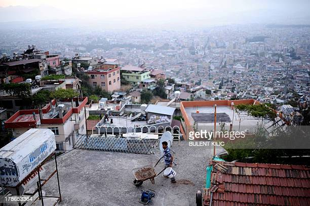 A man works on the roof overlooking the city of Antakya on August 29 2013 AFP PHOTO / BULENT KILIC