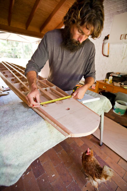 A man works on vintage 'Toothpick' wooden surfboard manufacture.