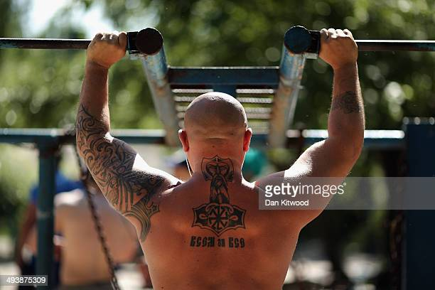 A man works out at Kachalka gym a Soviet era openair fitness area on the island of Tuhev on May 22 2014 in Kiev Ukraine The free park which was...