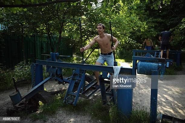 A man works out at Kachalka gym a Soviet era openair fitness area on the island of Tuhev on May 23 2014 in Kiev Ukraine The free park which was...