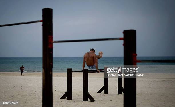 A man works out on a beach at the southern coastal Israeli city of Ashdod on November 22 a day after a cease fire was declared between the Jewish...