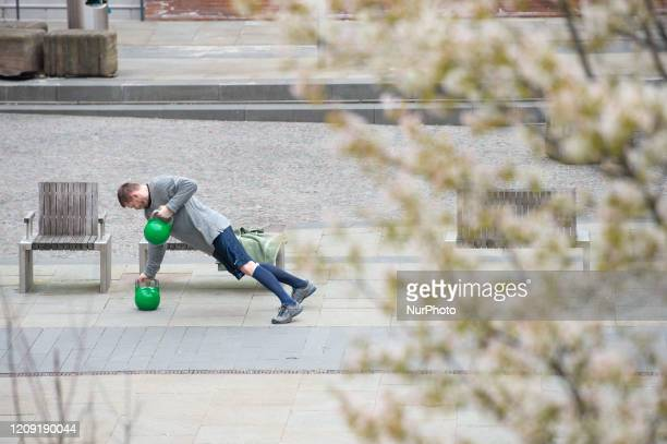 A man works out with kettlebells amidst the cherry blossom on Cutting Room Square in Ancoats Manchester city centre on Sunday 5th April 2020
