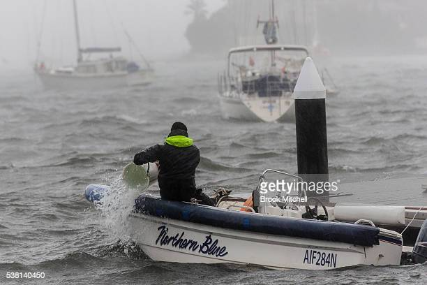 A man works to save his boat during wild weather on June 5 2016 in Sydney Australia The Bureau of Meteorology is forecasting up to 300mm of rain over...