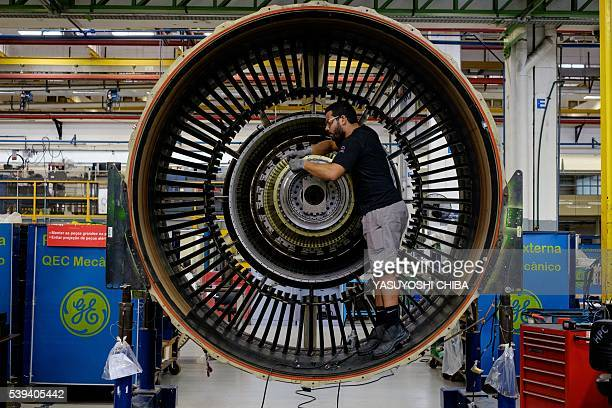 Man works with a jet engine at General Electric Celma, GE's aviation engine overhaul facility in Petropolis, Rio de Janeiro, Brazil on June 8, 2016....